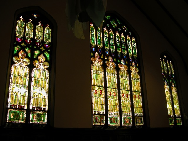 Stained glass, predominantly in greens and yellows, with a trefoil shape at the top of the bottom rung of panels and then arches above those.