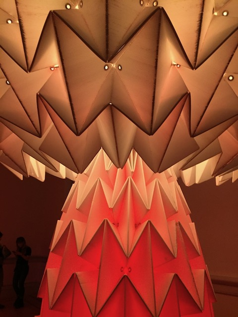 Photo of folded paper statue lit from within. The statue is larger than a person, and moves.
