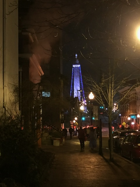 Photo showing the Washington Monument in Baltimore, MD, with purple Christmas lights strung up it. Ciy night scene, fog.