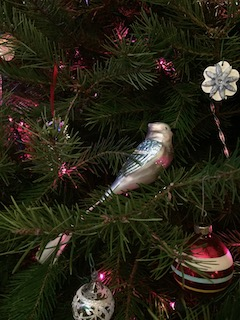 Photo of a glass bird, glass balls, and metal icicles on the branches of a fir tree.