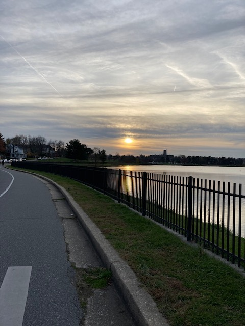 Photo of sunset on a cloudy day. Sun reflects in a reservoir. View is from a tarmac covered road next to the fence surrounding the water.