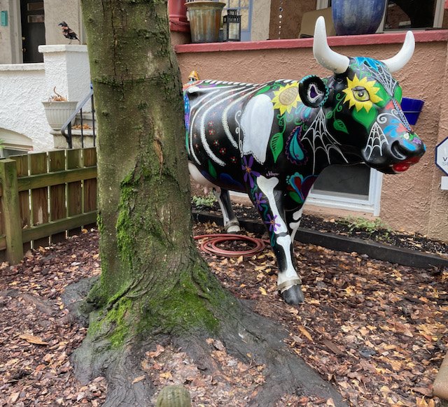 Fiberglass cow sculpture in a front yard. House porch is tan stucco. Cow has day of the dead imagery on it, including bones and fanciful flowers.
